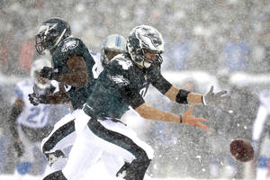Photo - In the snow, Philadelphia Eagles' Nick Foles cannot hang onto the ball during the first half of an NFL football game against the Detroit Lions, Sunday, Dec. 8, 2013, in Philadelphia. (AP Photo/Michael Perez)