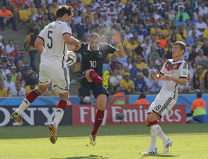 Photo - France's Karim Benzema, center, kicks up dust as he is challenged by Germany's Mats Hummels, left, and Toni Kroos during the World Cup quarterfinal soccer match between Germany and France at the Maracana Stadium in Rio de Janeiro, Brazil, Friday, July 4, 2014. (AP Photo/David Vincent)