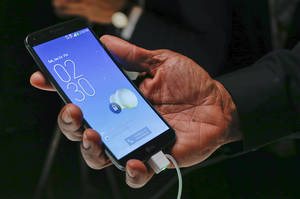 Photo - An LG representative holds an LG G Flex curved smartphone during the 2014 Consumer Electronics Show, Monday, Jan. 6, 2014, in Las Vegas. The phone, already available in some foreign markets, will debut in the United States in the Spring. (AP Photo/Julie Jacobson)