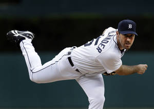 Photo - FILE - In this June 2, 2013, file photo, Detroit Tigers pitcher Justin Verlander throws a warmup pitch against the Cleveland Indians in the first inning of a baseball game in Detroit, Mich. Verlander underwent muscle repair surgery Thursday, Jan. 9, 2014, after injuring himself last month during offseason conditioning. (AP Photo/Paul Sancya, File)