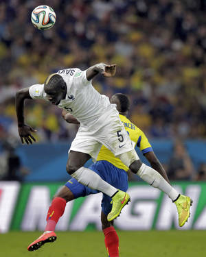 Photo - France's Mamadou Sakho collides with Ecuador's Enner Valencia as they try to head the ball during the group E World Cup soccer match between Ecuador and France at the Maracana Stadium in Rio de Janeiro, Brazil, Wednesday, June 25, 2014. (AP Photo/Bernat Armangue)