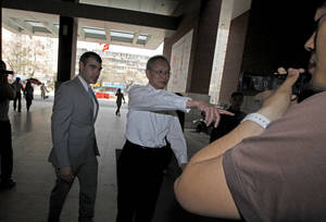 "Photo -   Robert S. Wang, center, deputy chief of mission at the U.S. embassy in Beijing, gestures as he walks with an unidentified U.S. embassy staff, left, outside the hospital where blind activist lawyer Chen Guangcheng is recuperating in Beijing Friday, May 4, 2012. The Chinese activist at the center of a diplomatic standoff between the United States and China said Friday his situation is ""dangerous,"" and that American officials have been blocked from seeing him for two days and friends who have tried to visit have been beaten up. (AP Photo/Ng Han Guan)"