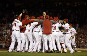 Photo - Members of the St. Louis Cardinals celebrate after the Cardinals' 7-0 win over the Chicago Cubs in a baseball game to clinch the NL Central title Friday, Sept. 27, 2013, in St. Louis. (AP Photo/Jeff Roberson)
