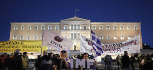 photo -   Demonstrators hold national and Syriza's party flag as well with anti austerity banners outside of the Greek Parliament in Athens on Sunday Nov. 11, 2012. Greece's lawmakers were set on Sunday to pass next year's austerity budget, extending tough spending cuts measures that have already left Greeks struggling as the country tries to slash its debts and pull itself out of a severe recession. (AP Photo/Petros Giannakouris)