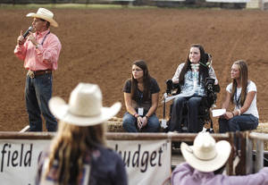 Photo - At the 2012 International Finals Youth Rodeo, Kelly Blanton is shown with friends Morgan Patton, second from left, and Bailey Hewat, right, as the announcer Monty Stueve, far left, relates how courageous Blanton is during her recovery from  injuries she suffered in 2011 in the IFYR practice arena. Photo Provided by Ed Blochowiak, Shawnee News Star <strong>Photo Provided by Ed Blochowiak - Photo Provided by Ed Blochowiak</strong>