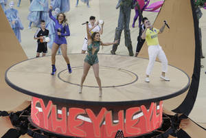 Photo - Brazilian singer Claudia Leitte, left, US singer Jennifer Lopez and rapper Pitbull perform during the opening ceremony ahead of the group A World Cup soccer match between Brazil and Croatia, the opening game of the tournament, in the Itaquerao Stadium in Sao Paulo, Brazil, Thursday, June 12, 2014. (AP Photo/Thanassis Stavrakis)