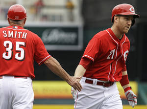 Photo - Cincinnati Reds' Todd Frazier (21) is congratulated by third base coach Steve Smith (35) after Frazier hit a two-run home run off Los Angeles Dodgers starting pitcher Zack Greinke in the first inning of a baseball game, Thursday, June 12, 2014, in Cincinnati. (AP Photo/Al Behrman)