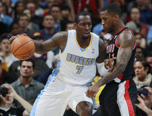 Photo - Denver Nuggets forward J.J. Hickson, left, works ball inside or shot as Portland Trail Blazers forward Thomas Robinson covers in the first quarter of an NBA basketball game in Denver, Tuesday, Feb. 25, 2014. (AP Photo/David Zalubowski)