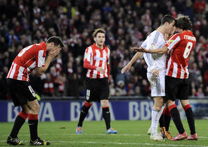 Photo - Real Madrid's Cristiano Ronaldo of Portugal, second right, discusses with Athletic Bilbao's Ander Iturraspe, right, after swiping his hand across the face of Athletic Bilbao's Carlos Gurpegi, left,  following a shove from his opponent, during their Spanish League soccer match against Athletic Bilbao, at San Mames stadium in Bilbao, Spain, Sunday, Feb. 2, 2014.  (AP Photo/Alvaro Barrientos)