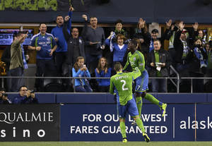 Photo - Seattle Sounders' Clint Dempsey (2) celebrates with Eddie Johnson, right, after Dempsey scored a goal in the first half of an MLS soccer match against the Los Angeles Galaxy, Sunday, Oct. 27, 2013, in Seattle. The goal was Dempsey's first since joining the Sounders earlier this season. (AP Photo/Ted S. Warren)