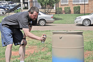 Photo - Joe Evans paints his rain barrel during a recent workshop. BY M. TIM BLAKE, FOR THE OKLAHOMAN