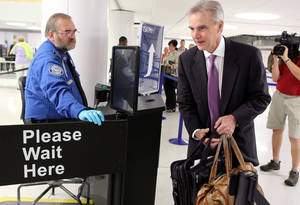 Photo - FILE - In this July 31, 2012 file photo, Transportation Security Administration agent Kevin Effan, left, allows a screened passenger to board his American Airlines flight via the new TSA PreCheck lane at Concourse C security checkpoint at Lambert-St. Louis International Airport on its first day of operation.  The TSA is expanding its PreCheck expedited screening program to passengers on international airlines. Air Canada on Tuesday, April 29, 2014 became the first international carrier to participate, with TSA officials saying other international airlines would soon sign on.  (AP Photo/St. Louis Post-Dispatch, Christian Gooden, File) EDWARDSVILLE INTELLIGENCER OUT; THE ALTON TELEGRAPH OUT