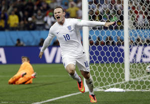 Photo - FILE - This is a Thursday, June 19, 2014   file photo of Uruguay's goalkeeper Fernando Muslera looks back as England's Wayne Rooney celebrates after scoring his side's first goal during the group D World Cup soccer match between Uruguay and England at the Itaquerao Stadium in Sao Paulo, Brazil.  Wayne Rooney was named England captain on Thursday, Aug. 28, 2014  taking over the leadership role of an inexperienced team in a rebuilding phase following its worst-ever World Cup. (AP Photo/Kirsty Wigglesworth, File)