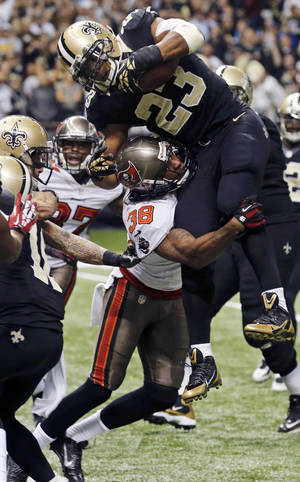 Photo - New Orleans Saints running back Pierre Thomas (23) leaps for a touchdown as Tampa Bay Buccaneers free safety Dashon Goldson (38) tries to keep him out of the end zone in the second half of an NFL football game, Sunday, Dec. 29, 2013, in New Orleans. (AP Photo/Bill Haber)