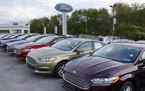 Photo - In this Wednesday, May 8, 2013 photo, new 2013 Ford Fusions are seen at an automobile dealer in Zelienople, Pa. U.S. auto sales slowed slightly in June 2014 but still maintained a healthy pace despite a record-setting string of safety recalls at General Motors and a slowdown in truck sales at Ford. Ford's U.S. sales chief John Felice said sales picked up at the end of June as automakers started promoting Independence Day sales. (AP Photo/Keith Srakocic)