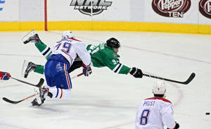 Photo - Dallas Stars center Tyler Seguin (91) takes a diving shot as Montreal Canadiens defenseman Andrei Markov (79), of Russia, defends during the second period of an NHL hockey game on Thursday, Jan. 2, 2014, in Dallas, Texas. (AP Photo/Sharon Ellman)