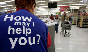 Photo - FILE - In this Sunday, Nov. 13, 2005, file photo, customers at a Wal-Mart store head to the checkout lines past a worker with the company's motto on the back of her vest, in Salt Lake City. With fewer middle-income jobs available, low-wage work is becoming a dead-end for more Wal-Mart employees. (AP Photo/Douglas C. Pizac, File)