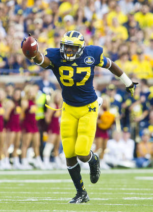 Photo - Michigan tight end Devin Funchess (87) celebrates after making a 22-yard reception for a first down in the fourth quarter of an NCAA college football game against Minnesota, Saturday, Oct. 5, 2013, in Ann Arbor, Mich. Michigan won 42-13. (AP Photo/Tony Ding)