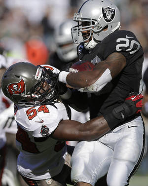 Photo -   Oakland Raiders running back Darren McFadden (20) is tackled by Tampa Bay Buccaneers outside linebacker Lavonte David (54) during the second quarter of an NFL football game in Oakland, Calif., Sunday, Nov. 4, 2012. McFadden left the game with a leg injury. The Raiders said he was questionable to return. (AP Photo/Marcio Jose Sanchez)