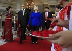 Photo -   U.S. Secretary of State Hillary Rodham Clinton leaves the Taj Hotel in Kolkata Monday, May 7, 2012. Clinton urged energy-starved India on Monday to reduce its Iranian oil imports to keep up pressure on the Islamic republic to come clean about its nuclear program. (AP Photo/Shannon Stapleton, Pool)