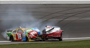 Photo - Kyle Busch (18) and Joey Logano (22) wreck during a NASCAR Sprint Cup series auto race at Kansas Speedway in Kansas City, Kan., Sunday, April 21, 2013. (AP Photo/Orlin Wagner)