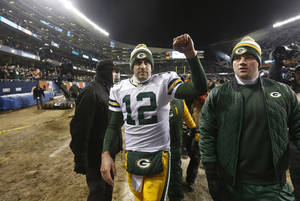 Photo - Green Bay Packers quarterback Aaron Rodgers (12) celebrates after an NFL football game against the Chicago Bears, Sunday, Dec. 29, 2013, in Chicago. The Packers won 33-28 to capture the NFC North title. (AP Photo/Charles Rex Arbogast)