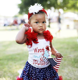 Photo - Makinzee Sigler, 1,  of Norman waves a flag at Norman's 4th of July celebration while dancing to music played by a live band at Reaves park. Photo by K.T. KING, The Oklahoman <strong></strong>
