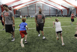 photo -   Detroit Lions defensive tackle Ndamukong Suh and teammate Tony Scheffler, left, instruct kids at the D1 Detroit training facility in Bloomfield Township, Mich., Tuesday, May 15, 2012. Suh and Scheffler are part-owners in the facility that will help any client from 7 and older to train as if they're preparing to be an elite athlete. (AP Photo/Carlos Osorio)