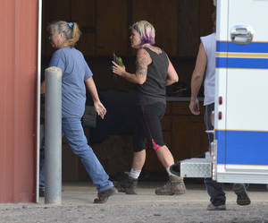Photo - This photo provided by the Imperial Republican shows kidnapping victim Julie Hanes, 38, of Lincoln after being released by her abductor and estranged husband in a massive manhunt for the pair. She is accompanied by Imperial EMS after being brought safely to the police staging area northwest of Imperial.(AP Photo/Imperial Republican, Russ Pankonin)