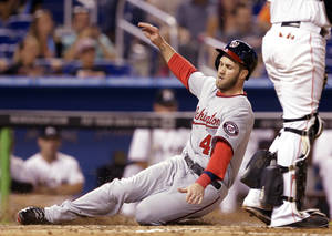 Photo - Washington Nationals' Bryce Harper scores on a throwing error by  Miami Marlins' center fielder Marcell Ozuna in the eighth inning during the of the MLB National League baseball game, Tuesday, April 15, 2014, in Miami. The Marlins defeated the Nationals 11-2. (AP Photo/Lynne Sladky)