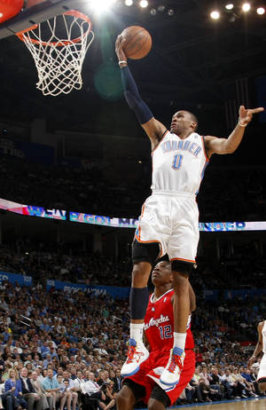 Photo - Oklahoma City's Russell Westbrook (0) goes past Los Angeles Clippers' Eric Bledsoe (12) during the NBA basketball game between the Oklahoma City Thunder and the Los Angeles at the Oklahoma City Arena, Wednesday, April 6, 2011. Photo by Bryan Terry, The Oklahoman