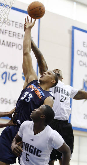Photo - Oklahoma City center Daniel Orton, center, leaps for a rebound with Orlando guard Victor Oladipo, front, and forward Romero Osby during a NBA Pro Summer League game last Monday.  AP Photo
