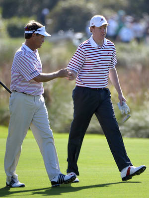 Photo - Davis Love III, left, and his son Dru walk down the eighth fairway during the first round of the Father/Son Challenge golf tournament in Orlando, Fla., Saturday, Dec. 15, 2012. The pair lead after the first round.(AP Photo/Phelan M. Ebenhack)