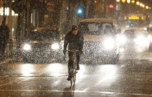 Photo - A lone cyclist works his way down Walnut Street, avoiding traffic but not the falling snow Thursday night, Jan. 2, 2014. (AP Photo/The Philadelphia Inquirer,Michael Bryant )  PHIX OUT; TV OUT; MAGS OUT; NEWARK OUT
