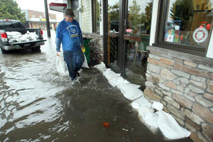 photo -   Building owner Darvin Ecklund places sandbags in front of the About Floors and West Sound Crossfit storefronts on Bay Street in Port Orchard, Wash., on Monday, Nov 19, 2012. Heavy rains inundated the areas storm drains and caused flooding in the Port Orchard downtown district and elsewhere in Kitsap County. (AP Photo/Kitsap Sun, Meegan M. Reid)
