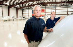 Photo - Bill Christiansen (left) and his son Bryan stand in one of the hangars owned by Christiansen Aviation on the grounds of Jones Riverside Airport at Jenks.?MICHAEL WYKE/Tulsa World   <strong></strong>