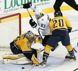 Photo -   Dallas Stars center Mike Ribeiro (63) is tripped up by Nashville Predators defenseman Ryan Suter (20) as goalie Pekka Rinne (35), of Finland, blocks a shot by Ribeiro in the third period of an NHL hockey game on Thursday, April 5, 2012, in Nashville, Tenn. The Predators won 2-0. (AP Photo/Mark Humphrey)