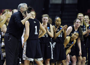 Photo - Army head coach Dave Magarity, left, hugs senior Jen Hazlett as she exits the game during the second half of the first round of the NCAA women's college basketball game against Maryland tournament on Sunday, March 23, 2014, in College Park, Md. Maryland won 90-52. (AP Photo/Gail Burton)