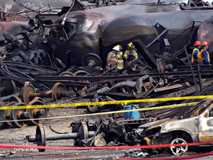 Photo - Crews move through the debris Tuesday, July 16, 2013, as work continues at the crash site of the train derailment and fire in Lac-Megantic, Quebec.  The July 6, 2013 derailment left 37 people confirmed dead and another 13 missing and presumed dead.  (AP Photo/Ryan Remiorz, Pool)
