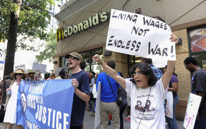 Photo - Azi Ebrahimi, right, demonstrates for higher wages for fast food industry workers during a one day strike coinciding with strikes at other fast food restaurants across the country, Thursday, Aug. 29, 2013, in Atlanta. (AP Photo/John Amis)