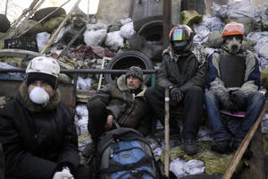 Photo - Anti-government protesters take a break on a barricade at Independence Square in Kiev, Ukraine, Friday, Feb. 21, 2014. Ukraine's presidency said Friday that it has negotiated an international deal intended to end battles between police and protesters that have killed scores and injured hundreds. (AP Photo/ Marko Drobnjakovic)