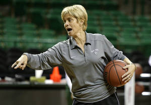 Photo - Baylor head coach Kim Mulkey instructs her team during practice at the NCAA women's college basketball tournament, Friday, March 21, 2014, in Waco, Texas. Mulkey will not coach the first-round game scheduled to be played Saturday against Western Kentucky. Mulkey was suspended for the game after criticizing officiating in the 2013 NCAA playoffs. (AP Photo/Tony Gutierrez)