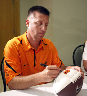 Photo - Oklahoma State University college football head coach Mike Gundy signs autographs during OSU's caravan at the National Cowboy & Western Heritage Museum in Oklahoma City , Wednesday, Aug. 3, 2011. Photo by Sarah Phipps, The Oklahoman ORG XMIT: KOD