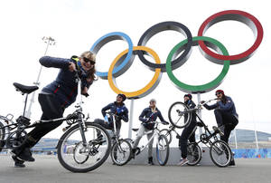 Photo - Team USA speed skaters, from left, Sugar Todd of Milwaukee, Wis., Aly Dudek of Hales Corner's, Wis., Emily Scott of Springfield, Mo., Heather Richardson of Highpoint, N.C., and Brittany Bowe of West Jordan, Utah, pose at the Olympic rings ahead of the 2014 Winter Olympics, Wednesday, Feb. 5, 2014, in Sochi, Russia. The skaters were taking a break from training to ride bicycles around Olympic Park. (AP Photo/Robert F. Bukaty)