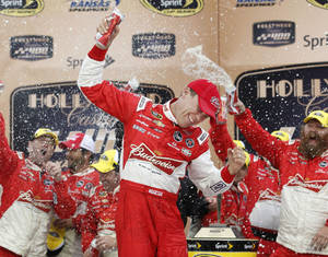Photo - Driver Kevin Harvick celebrates in victory lane after winning the Hollywood Casino 400 NASCAR Sprint Cup series auto race at Kansas Speedway in Kansas City, Kan., Sunday, Oct. 6, 2013. (AP Photo/Colin E. Braley)
