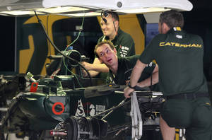 photo -   Crew members of Caterham Formula One team work on their car at the Buddh International Circuit in Noida, on the outskirts of New Delhi, India, Wednesday, Oct. 24, 2012. The second Indian Formula One Grand Prix is scheduled for Oct. 26-28. (AP Photo/ Manish Swarup)
