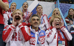 Photo - Evgeni Plushenko of Russia, front left, and other team members cheers for Julia Lipnitskaia of Russia as she competes in the women's team free skate figure skating competition at the Iceberg Skating Palace during the 2014 Winter Olympics, Sunday, Feb. 9, 2014, in Sochi, Russia. (AP Photo/Darron Cummings, Pool)