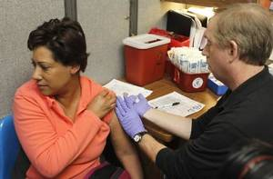 Photo - Karen Woodard receives a flu vaccination from public health nurse David Legg at the Oklahoma City County Health Department in Oklahoma City, OK, Thursday, January 3, 2013, By Paul Hellstern
