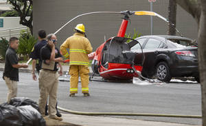 Photo - The wreckage of a small helicopter that crashed sits next to a car in downtown Honolulu Wednesday, May 8, 2013. The helicopter crashed near the intersection of Fort Street and Beretania Street. The condition of the pilot is unknown. (AP Photo/Eugene Tanner)