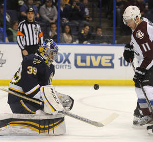 Photo - St. Louis Blues' goalie Ryan Miller (39) blocks a shot by Colorado Avalanche's Jamie McGinn (11) during the first period of an NHL hockey game, Saturday, April 5, 2014, in St. Louis. (AP Photo/Bill Boyce)
